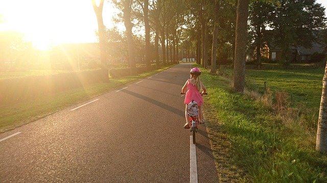 Mädchen mit Kinderfahrrad unterwegs