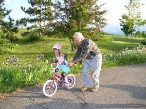 Opa mit Enkeltochter beim Fahrrad fahren